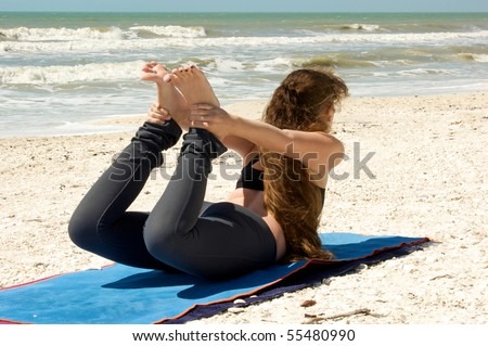 Brunette caucasian woman with long hair on beach doing Bow Yoga Pose, Dhanurasa,  on mat in the florida in the gulf of mexico - stock photo