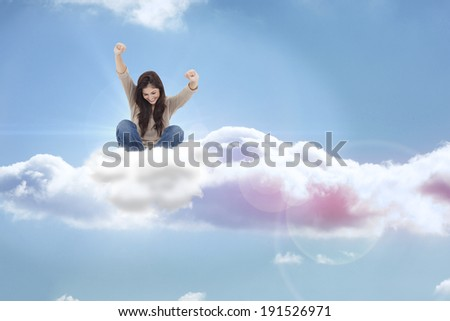 Brunette cheering while using laptop against beautiful blue sky with clouds - stock photo
