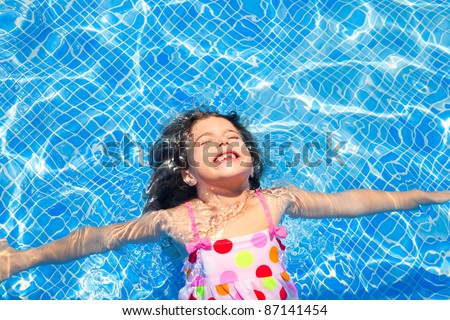 brunette children girl swimming in blue tiles pool floating closed eyes - stock photo