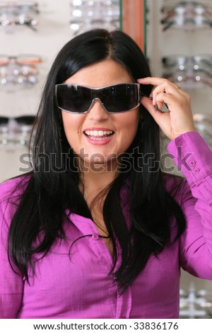 brunette chooses collets to glasses - stock photo