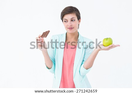 Brunette choosing between an apple and chocolate bar on white background - stock photo