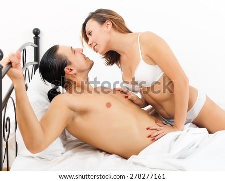 Brunette couple having sex on white sheet in bed   - stock photo