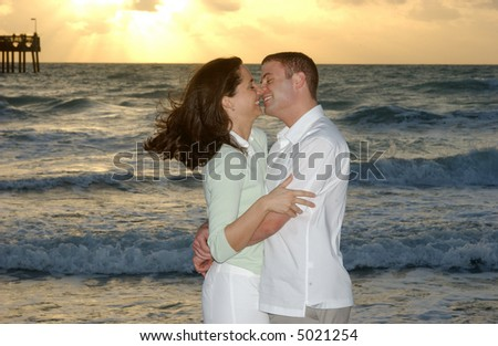 Brunette Couple Kissing at the Beach at Sunrise