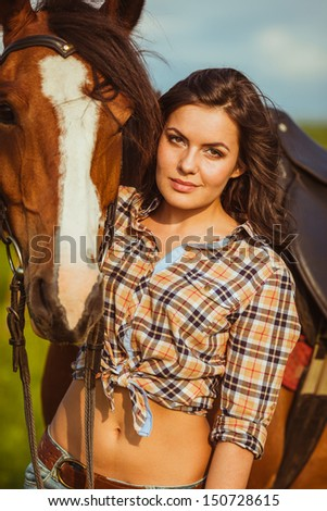 brunette cowgirl woman posing with horse outdoors closeup portrait - stock photo
