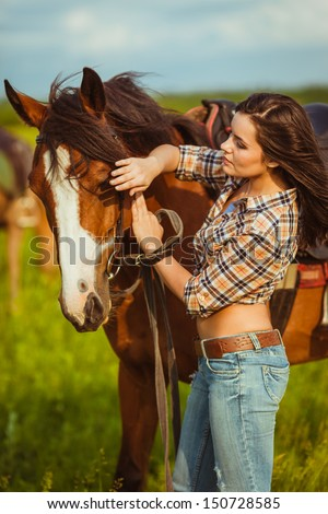brunette cowgirl woman standing with horse outdoors portrait - stock photo