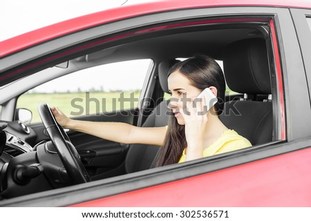 Brunette driving a red car and speaks on a mobile phone. - stock photo