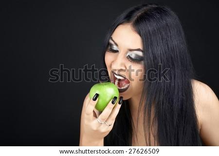 Brunette eating a green apple - stock photo