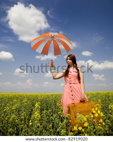 Brunette enchantress with umbrella and suitcase at spring rapeseed field.