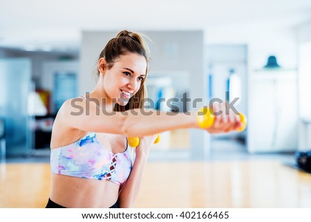 Brunette european woman exercising with light yellow weights at the gym - stock photo