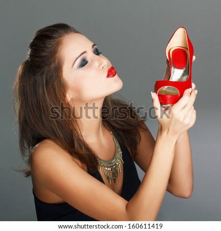 Brunette fashionable woman holding red high heels, shopping - stock photo