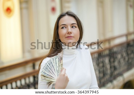 Brunette female holding and showing dollars with happy face and toothy smile while looking at camera  - stock photo