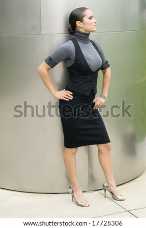 Brunette female standing outside with hands on hips - stock photo