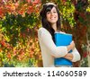 Brunette female student smiling on autumn background and holding notebook - stock photo