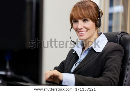 Brunette female support assistant working at the help desk - stock photo