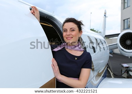 Brunette flight attendant looking out the open doors of the small jet plane - stock photo
