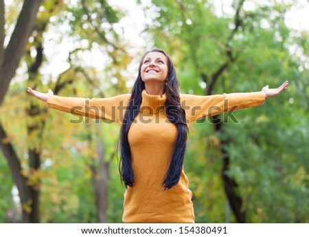 Brunette girl at autumn alley in the park - stock photo