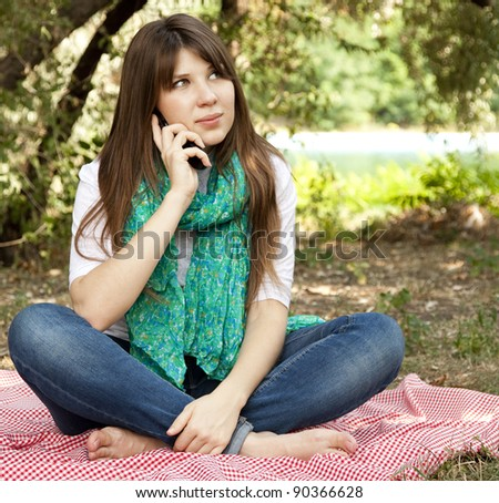 Brunette girl at outdoor colling by phone. Autumn.
