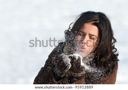 Brunette girl blowing on the snowflakes