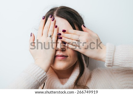 brunette girl closed her eyes with her hands on a white background - stock photo