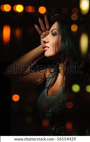 brunette girl dancing with colorful lights background - stock photo