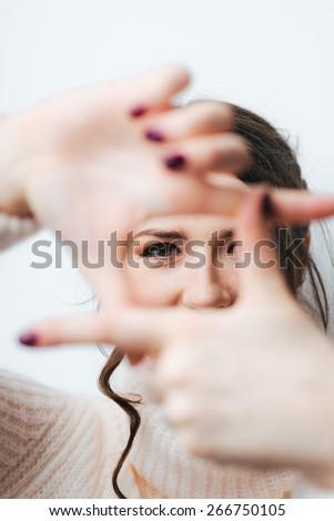 brunette girl doing camera hands and fingers on a white background - stock photo