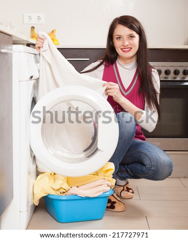 brunette girl doing laundry with washing machine