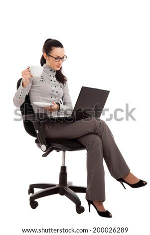 brunette girl drinking coffe, sitting in the chair with laptop over white background - stock photo
