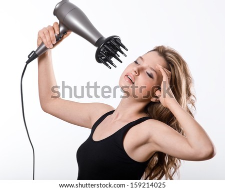 Brunette girl dry with hairdryer their long hair,  isolated on white background