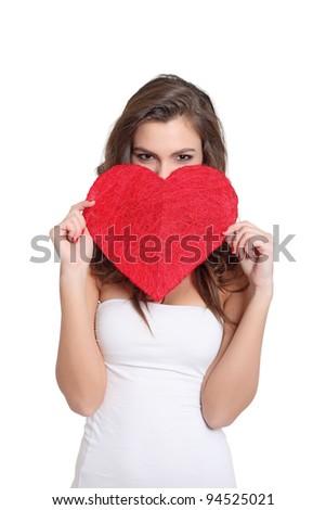Brunette girl hiding behind a big heart - stock photo