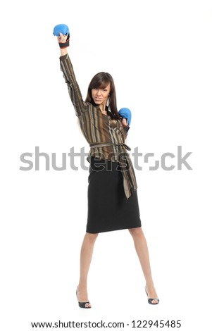 Brunette girl in a business suit with boxing gloves raised her arms up in triumph