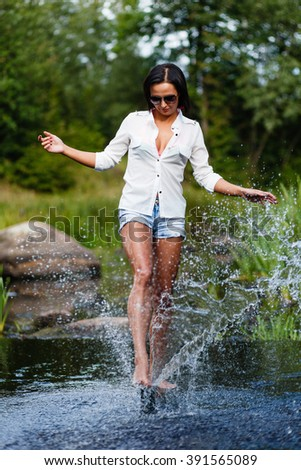 Brunette girl in a white shirt and jeans shorts. - stock photo