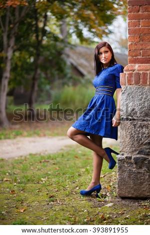 Brunette girl in blue dress near a brick wall. - stock photo