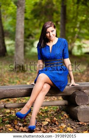Brunette girl in blue dress sitting on bench at autumn park. - stock photo