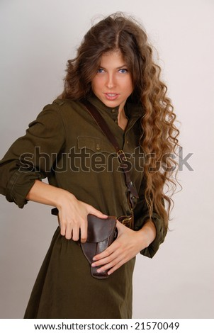 brunette girl in military clothes on the grey background