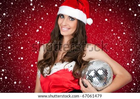 brunette girl in santa costume holding disco ball - stock photo