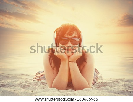 Brunette girl in sunglasses and headphones on the beach in sunset time. - stock photo