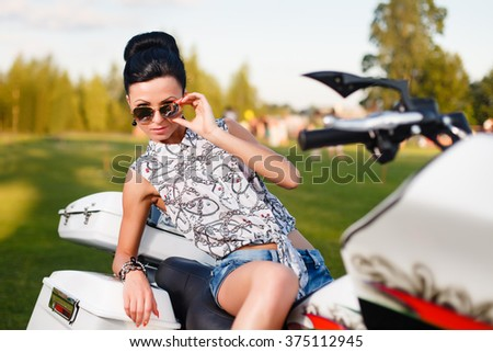 Brunette girl in sunglasses on white chopper.