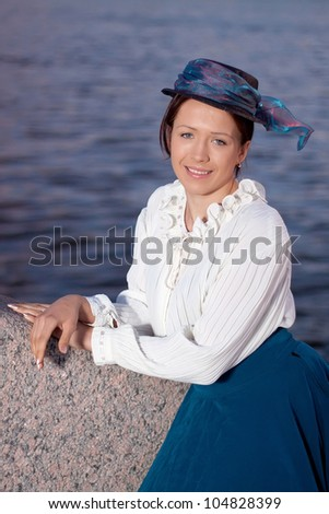 Brunette girl in the clothes in the retro style near the river Neva in St.Petesburg, Russia. - stock photo