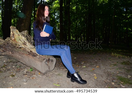 Brunette girl in the forest holding a book in his hands