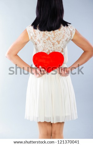Brunette girl in white dress with red Valentine heart. Rear view. - stock photo