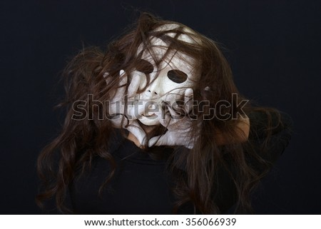 brunette girl is holding a theatrical mask