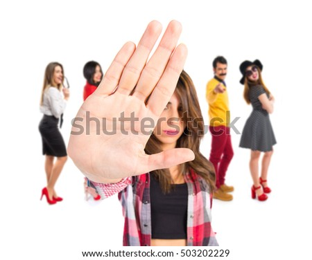 Brunette girl making stop sign with many people behind