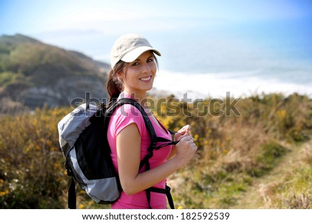 Brunette girl on a hiking day with backpack - stock photo