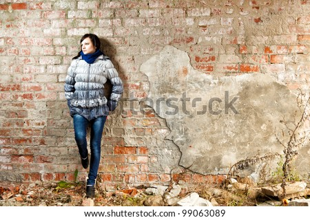 Brunette girl posing at abandoned ruins. - stock photo