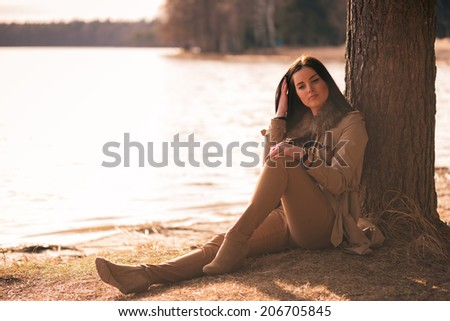 Brunette girl sitting under the tree on a lake shore