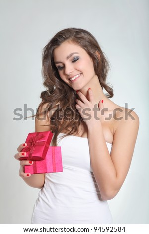 Brunette girl smiling with a red box - stock photo