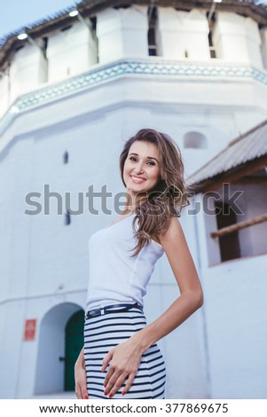 brunette girl standing on the background of the castle walls