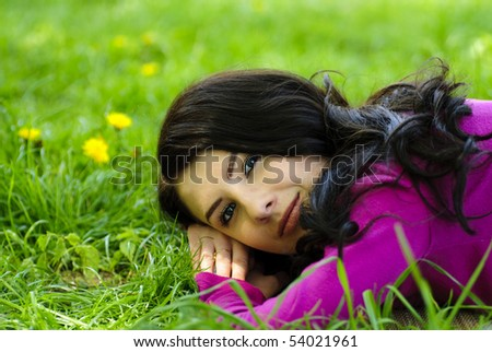 Brunette girl take pleasure on the grass with dandelions, outdoor portrait. Close up face