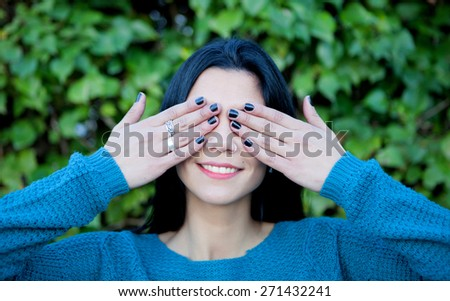 Brunette girl with a piercing covering her eyes  - stock photo