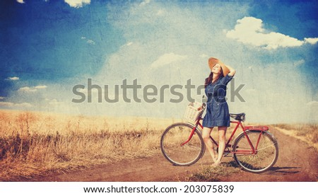 Brunette girl  with  bycicle on countryside road. - stock photo